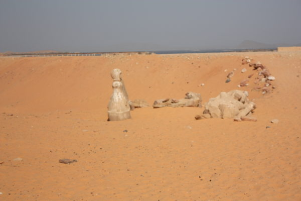Statues covered by sand in Egypt